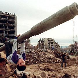 Sarajeve vaikas žaidžia ant palikto tanko vamzdžio