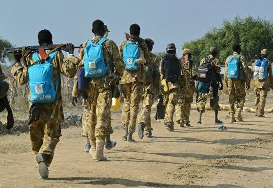 """AFP/""""Scanpix"""" nuotr./Pietų Sudano kariai su žydromis UNICEF kuprinėmis"""