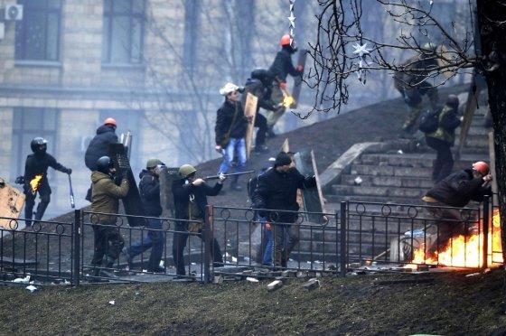 """AFP/""""Scanpix"""" nuotr./Ginkluoti protestuotojai artinasi prie milicininkų"""