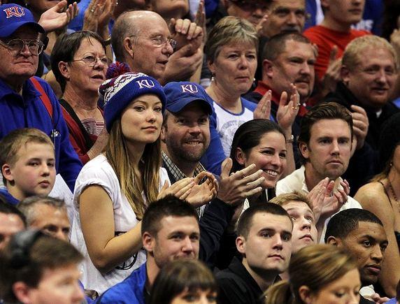 AFP/Scanpix nuotr./Mėlynomis kepuraitėmis pasipuoaę Jasonas Sudeikis ir Olivia Wild stebi krepainio rungtynes.