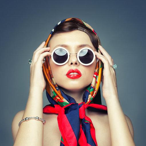 """""""Shutterstock"""" nuotr./Pridėkite prie bet kokio niūriausio kasdienio įvaizdžio skarelę, surištą kaip nuotraukoje, akinius kontrastingais rėmais ir lūpdažį. Štai jūs – retro """"diva""""!"""
